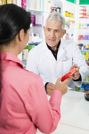 Pharmacist Showing Product To Female Customer