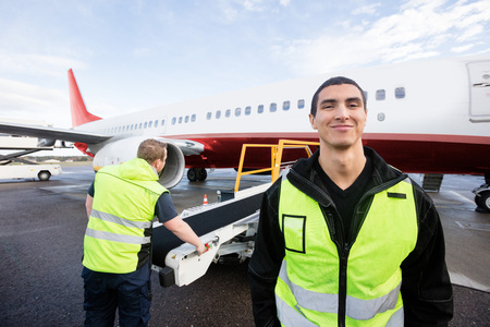 Worker Smiling While Colleague Working On Runway Stock Photo