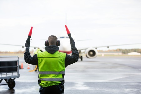 Ground Crew Signaling To Airplane Stockfoto