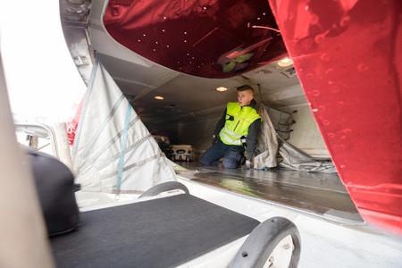 Male Worker Kneeling In Airplane