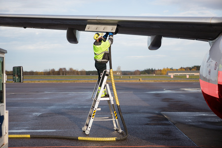 Male Worker Refueling Airplane While Standing On Step Ladder