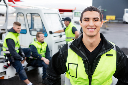 Confident Worker Smiling While Colleagues Communicating At Gangw
