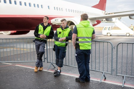 Crew Members Standing By Fence Against Airplane