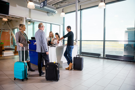 Passengers With Luggage Standing While Receptionists Working At