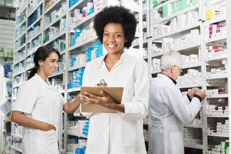 Female Chemist Writing On Clipboard While Colleagues Counting St Stock Photo