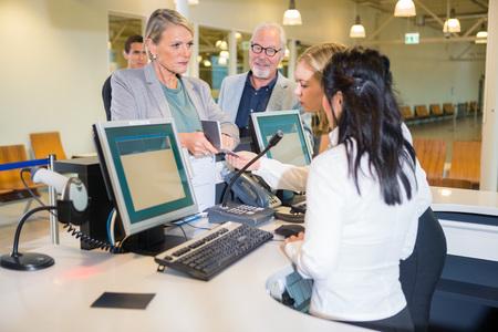Ernstige Onderneemster die Paspoort toont aan Personeel bij Luchthaven