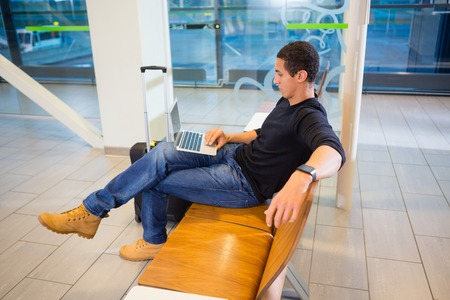 Man Using Laptop In Airport Waiting Area