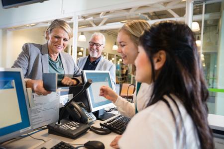 Zakenvrouw bedrijf paspoort terwijl personeel op luchthaven werkt Stockfoto
