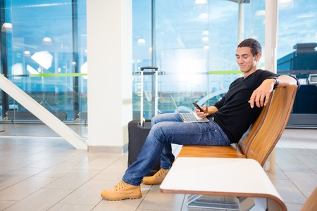 Young Man With Mobile Phone And Laptop At Airport