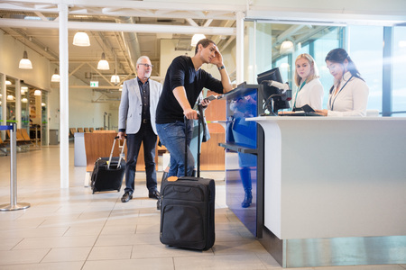 Staff Checking Passport Of Male Passenger At Counter In Airport Standard-Bild