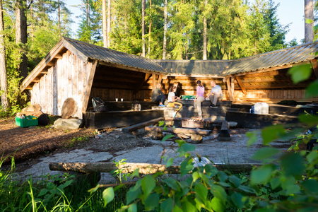 Friends Preparing Food By Shed In Forest Archivio Fotografico