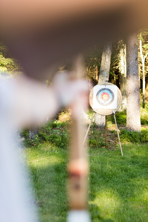 Young Man Aiming Arrow At Target Board In Forest Archivio Fotografico