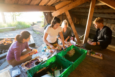 Coworkers Preparing Food In Shed At Forest Archivio Fotografico