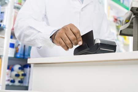 selling service: Midsection Of Pharmacist Swiping Credit Card On Reader