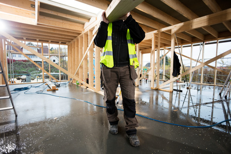 Low Section Of Male Carpenter Carrying Wooden Plank