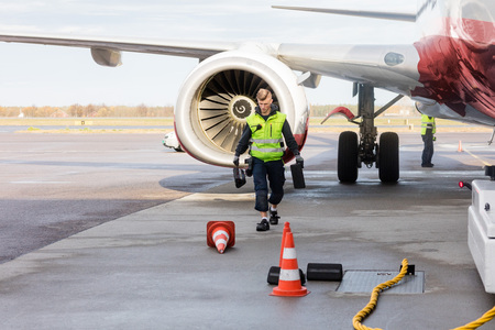 Worker Carrying Chocks By Airplane On Wet Runway