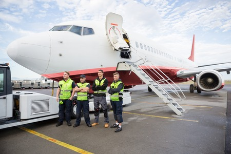 Confident Ground Team Standing Arms Crossed Against Airplane