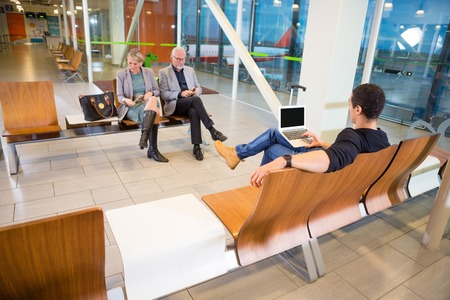 Passengers Using Technologies In Airport Waiting Area