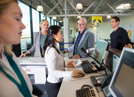 Staff Checking Passport On Computer While Passengers Waiting In