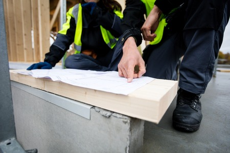 Closeup Of Carpenter Pointing On Plan By Colleague At Site