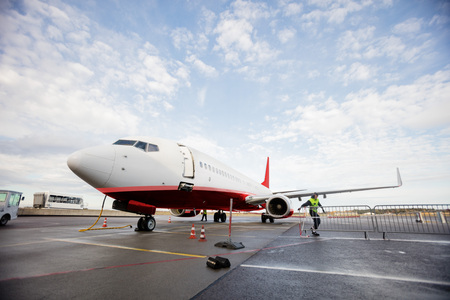 Commercial Airplane On Wet Runway Against Cloudy Sky Archivio Fotografico