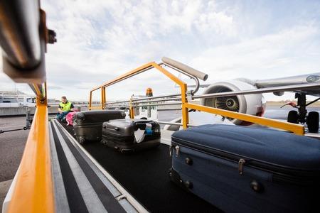 Baggage On Conveyor Belt Being Unloaded Archivio Fotografico