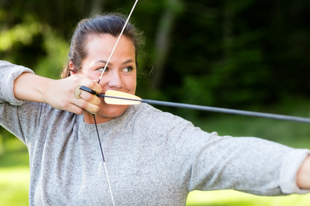 Confident Athlete Aiming With Bow And Arrow In Forest