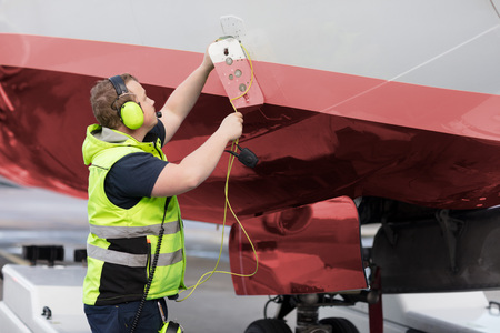 Ground Staff Member Adjusting Communication Cable On Outer Airpl Archivio Fotografico