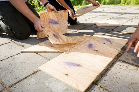 Cropped Image Of Friends Arranging Wooden Puzzle On Patio