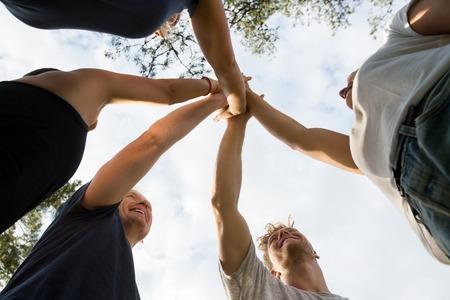 faible angle de vue des amis empilant les mains contre le ciel