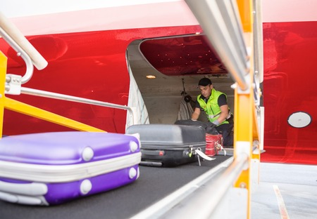 Worker Placing Bags On Conveyor To Unload Airplane