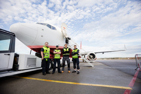 Confident Ground Crew Standing Arms Crossed Against Airplane