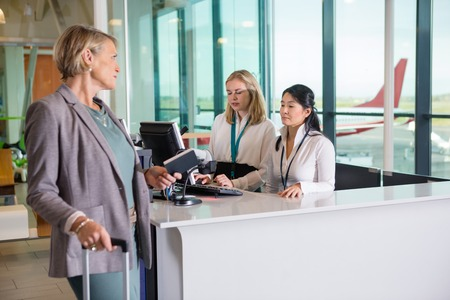 Passenger Looking At Receptionists Working At Airport Counter