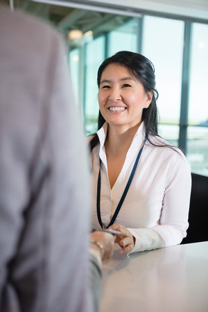 Happy Receptionist Looking At Businesswoman At Airport Counter Archivio Fotografico