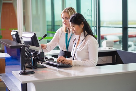 Female Ground Staff Using Computer At Counter In Airport Stock Photo