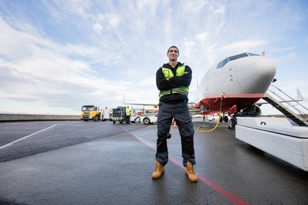 Confident Male Worker Standing Arms Crossed On Wet Runway
