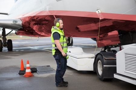 Ground Worker Standing By Airplane With Communication Cable On R Stock Photo