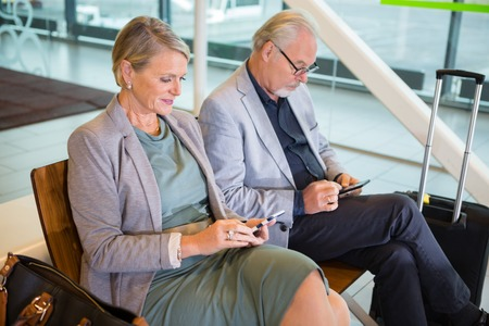 Senior Business Couple Using Mobile Phones In Airport Lobby