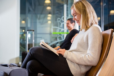 Side View Of Smiling Woman Reading Book At Airport Archivio Fotografico