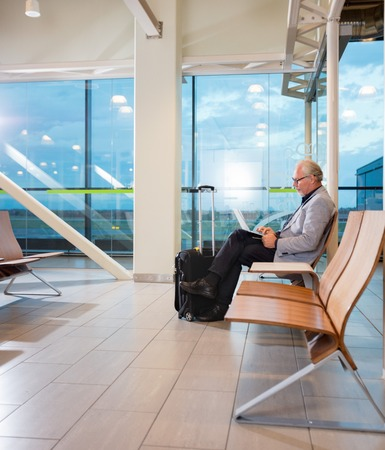 Senior Businessman Using Laptop At Airport Terminal Archivio Fotografico