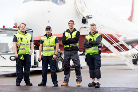 Ground Members With Arms Crossed Standing Against Airplane