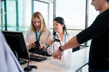 Receptionist Scanning Passengers Smart Watch While Colleague Che Archivio Fotografico