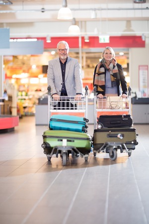 Happy Senior Business Couple With Luggage In Trolleys At Airport