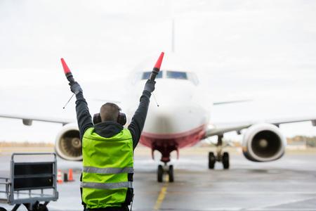Ground Crew Signaling To Airplane On Runway Archivio Fotografico