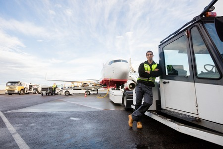 Worker Leaning On Truck With Airplane In Background