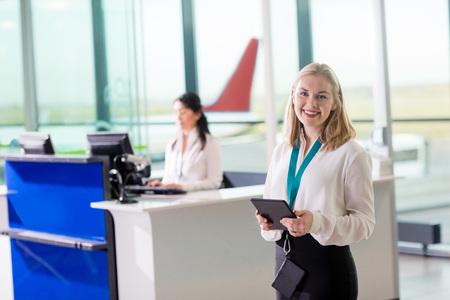 Personal de tierra joven que sostiene la tableta digital en el aeropuerto Foto de archivo - 87040562