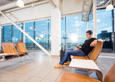 Man Using Mobile Phone In Airport Waiting Area Archivio Fotografico