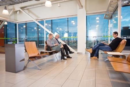 Passengers Waiting For Flight At Airport Terminal