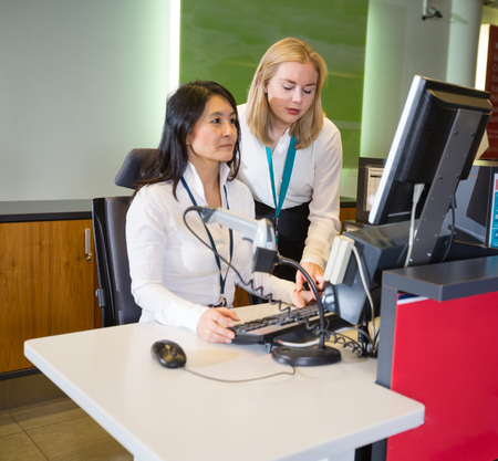 Female Staff Working At Airport Check-in Desk