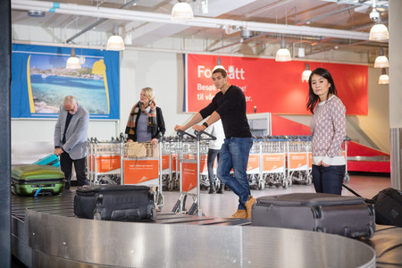 Tourists Waiting For Luggage From Conveyor Belt At Airport